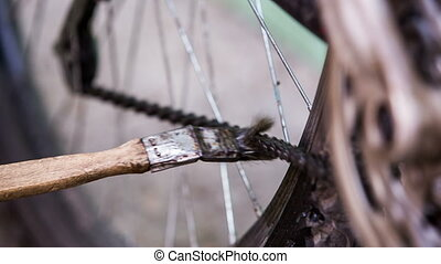 Cyclist Cleaning Bicycle Chain With Brush - This is a...