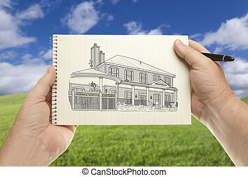 Hands Holding Paper With House Drawing Over Empty Grass Field