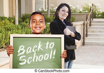 Boy Holding Back To School Chalk Board with Teacher Behind