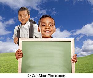 Happy Hispanic Boys In Grass Field Holding Blank Chalk Board...