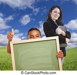 Young Boy with Blank Chalk Board, Teacher Behind on Grass