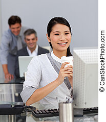 Young Businesswoman drinking a coffee at her desk in the...
