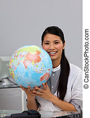 Confident asian businesswoman holding terrestrial globe in...