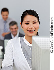 Smiling asian businesswoman working at a computer with her...