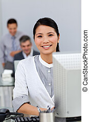 Charming asian businesswoman working at a computer with her...