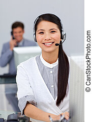 Cheerful young businesswoman with headset on at a computer