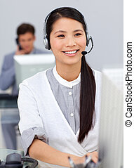 Smiling businesswoman with headset on at a computer