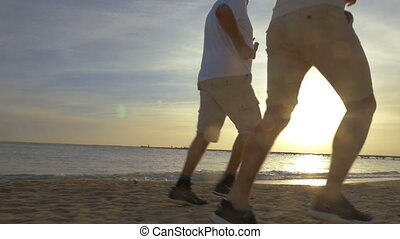 Two Men Jogging on the Beach - Low-angle steadicam shot of...
