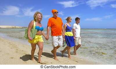 Young and senior people walking at the seaside together