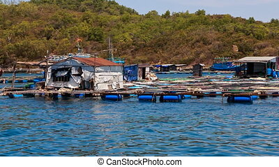view of vietnamese houses on rafts against boats and hills -...