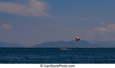 view of kite surfing against blue sky and mountains -...