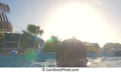 Boy Swimming on Fathers Back - Slow motion shot of a little...