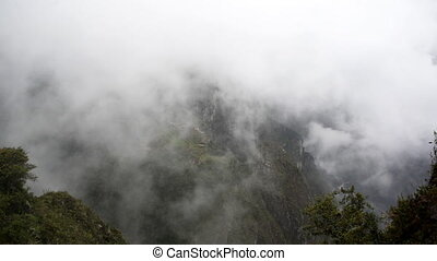 Foggy Machu Picchu - Fog and clouds passing by the ruins of...