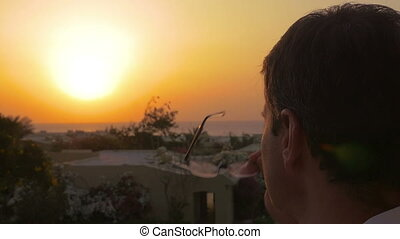 Man putting on spectacles to enjoy the sunset