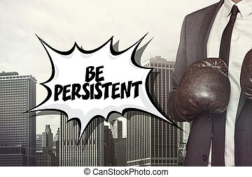 Be persistent text with businessman wearing boxing gloves on...