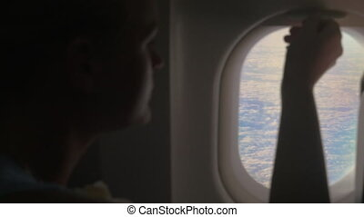 Woman looking out illuminator in plane