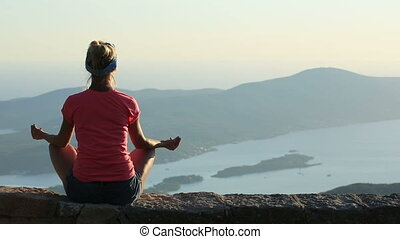 Woman meditating on top of a rock at the mountains in...