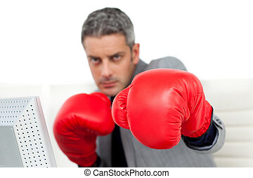 Self-assured businessman with boxing gloves in the office