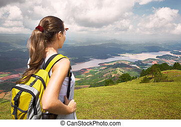 Young woman hiker with backpack standing on top of the mountain and enjoying valley view