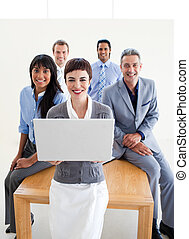 Smiling business people using a laptop in the office