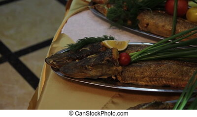 fried pike decorated with verdure at restaurant