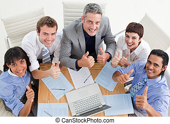 High angle of a cheerful business team with thumbs up in a...