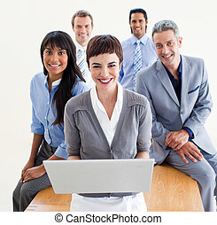 Joyful business people standing around a desk looking at a...