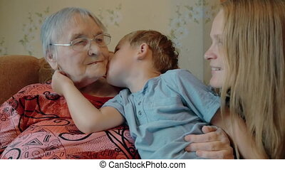 Little boy expressing love to mother and grandmother with...