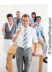 Multi-ethnic business people toasting with Champagne in the...