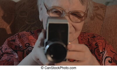 Senior woman filming with retro video camera - Slow motion,...