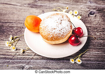 Donut on white plate with fruits on wooden background
