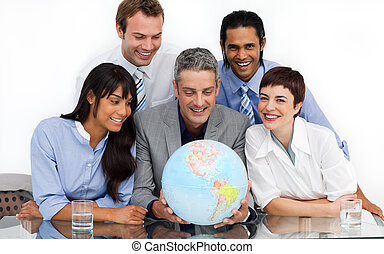 A business group showing diversity looking at a terrestrial globe in the office