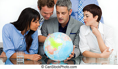 International business people looking at a terrestrial globe...