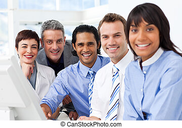 Multi-ethnic smiling business team sitting in a row in the...