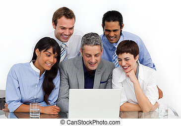 A business group showing diversity using a laptop in the...