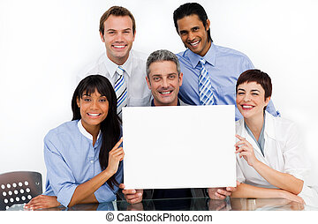A business group showing diversity holding a white card in...