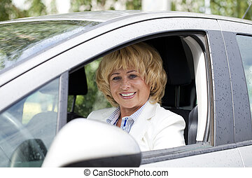Old happy elderly driver woman 55-60 years in jacket Driving...