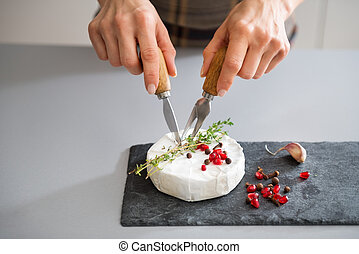 Woman's hands using cheese knife and fork to cut Camembert -...