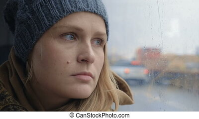 Frustrated and sad woman traveling by bus on rainy day -...