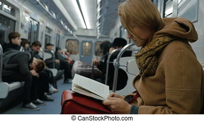 Young woman reading a book in subway