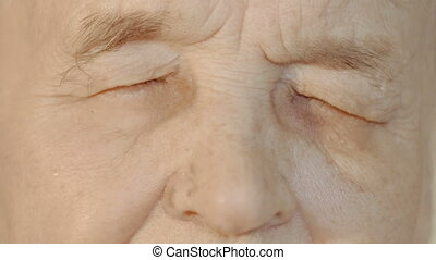 Senior woman opening and closing eyes - Slow motion and...