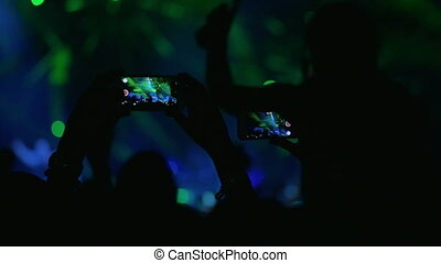 People with mobiles shooting laser show on the concert -...