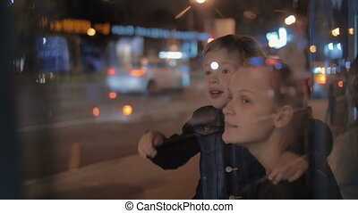 Mother and curious son in night city - Slow motion of mother...