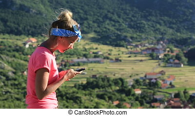 girl uses smartphone infront of beautiful view in Montenegro