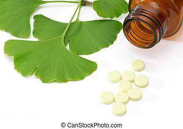Ginkgo pills - Fresh ginkgo leaves with pills and brown...