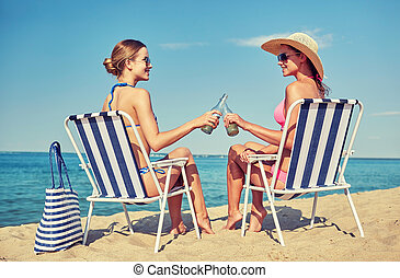 happy women clinking bottles and drinking on beach - summer...