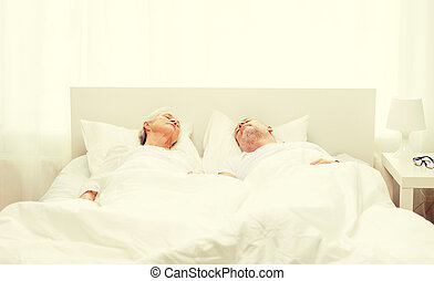 happy senior coupler lying in bad at home - family, bedtime,...