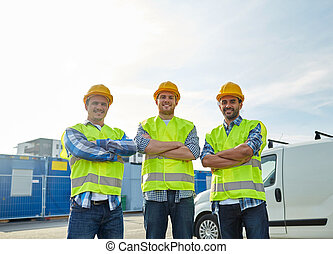 happy male builders in high visible vests outdoors -...