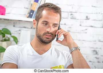 portrait of a young businessman on phone in his office