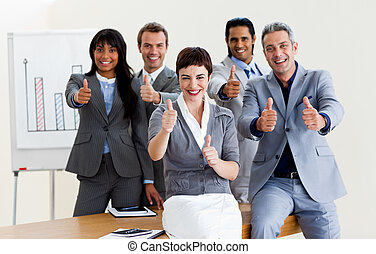 Successful business people with thumbs up smiling at the...